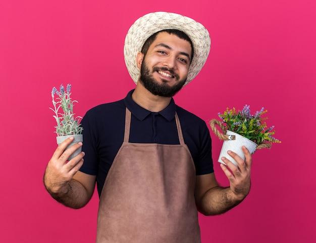 Glimlachende jonge kaukasische mannelijke tuinman die tuinierhoed draagt die bloempotten houdt die op roze muur met exemplaarruimte worden geïsoleerd