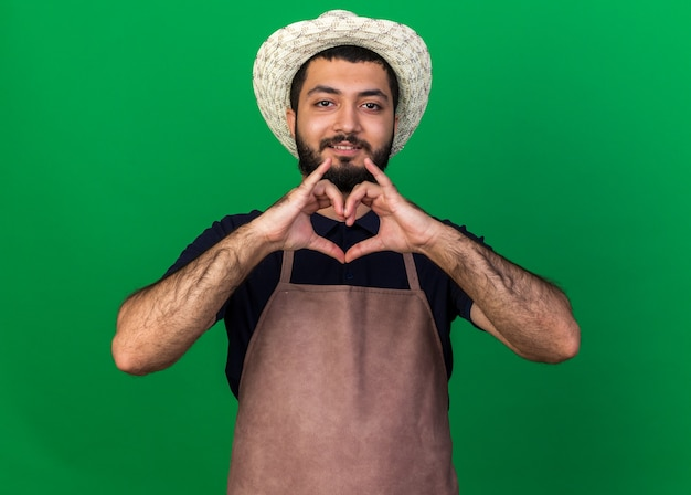 Glimlachende jonge kaukasische mannelijke tuinman die tuinierhoed draagt die hartteken gebaart dat op groene muur met exemplaarruimte wordt geïsoleerd