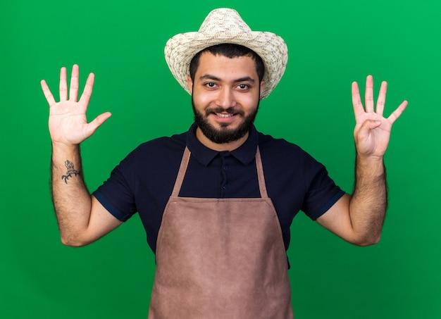 Glimlachende jonge kaukasische mannelijke tuinman die tuinierhoed draagt die negen met vingers gebaart die op groene muur met exemplaarruimte worden geïsoleerd