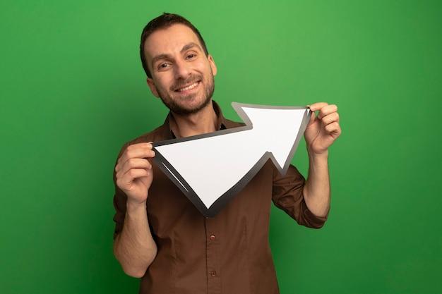 Glimlachende jonge kaukasische mens die de pijlteken van de cameraholding bekijkt die naar kant wijst die op groene achtergrond met exemplaarruimte wordt geïsoleerd