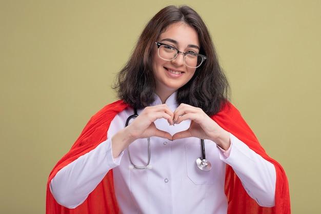 Glimlachende jonge kaukasische superheldenvrouw in rode cape die doktersuniform en stethoscoop draagt met een bril die hartteken doet
