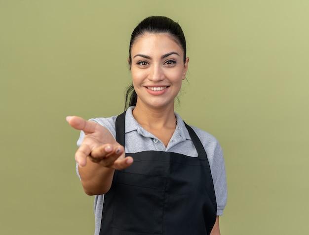 Glimlachende jonge kaukasische vrouwelijke kapper die uniform draagt en hand uitstrekt naar geïsoleerd op olijfgroene muur met kopieerruimte copy