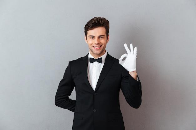 Glimlachende jonge kelner die ok gebaar tonen.