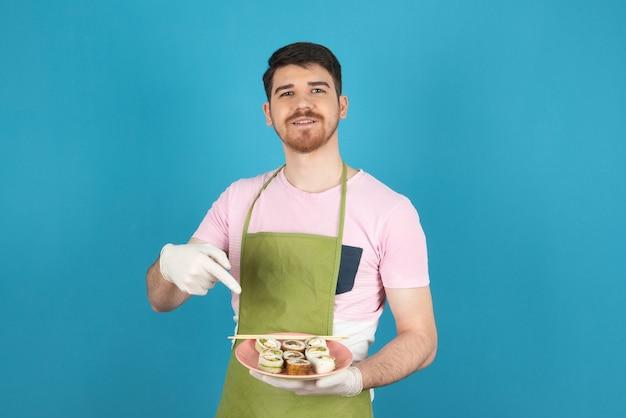 Glimlachende jonge kerel die cakeplakken vasthoudt en er met de vinger naar wijst.