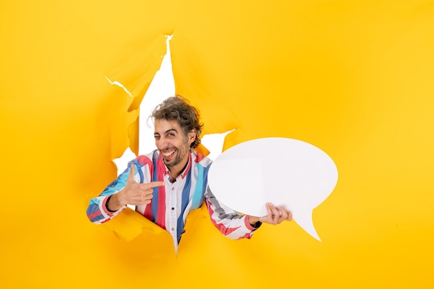 Glimlachende jonge kerel die een witte pagina met vrije ruimte aanwijst en iets aan de linkerkant wijst in een gescheurd gat in geel papier