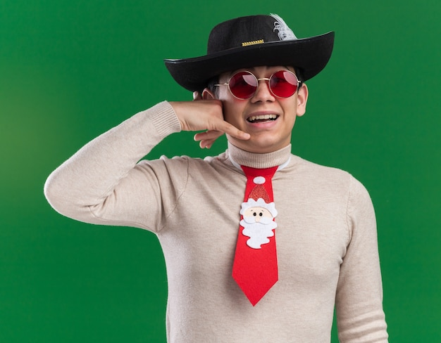Glimlachende jonge kerel die hoed met kerstmisband en bril draagt die telefoongesprekgebaar toont dat op groene muur wordt geïsoleerd