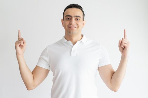 Glimlachende jonge kerel die naar omhoog en camera bekijken richten