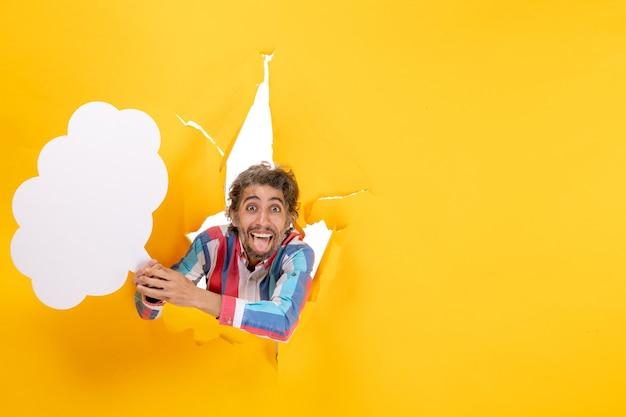 Glimlachende jonge kerel die wit wolkvormig papier vasthoudt en poseert voor de camera in een gescheurd gat en een vrije achtergrond in geel papier
