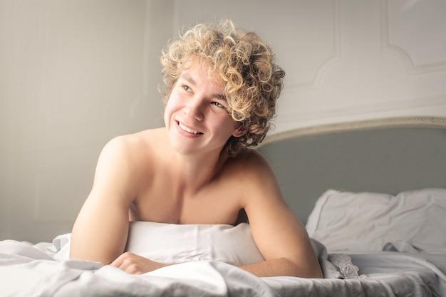 Glimlachende jonge kerel in bed