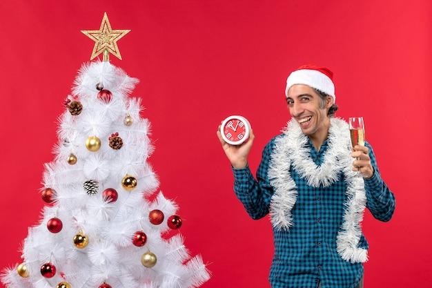 Glimlachende jonge kerel met de hoed van de kerstman en een glas wijn en het houden van klok die zich dichtbij kerstboom op rood bevindt