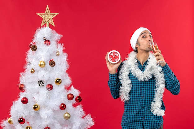 Glimlachende jonge kerel met de hoed van de kerstman en genietend van een glas wijn en het houden van klok die zich dichtbij kerstboom op rood bevindt