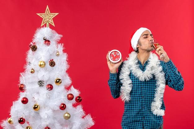 Glimlachende jonge kerel met de hoed van de kerstman en het drinken van een glas wijn en het houden van klok die zich dichtbij kerstboom op rood bevindt