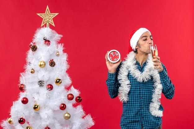 Glimlachende jonge kerel met de hoed van de kerstman en het proeven van een glas wijn en het houden van klok die zich dichtbij kerstboom op rood bevindt
