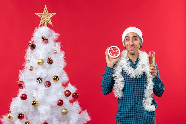 Glimlachende jonge kerel met de hoed van de kerstman en met een glas wijn en een klok die zich dichtbij kerstboom op rood bevinden