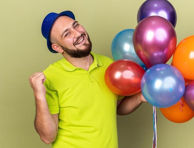 Glimlachende jonge kerel met feestmuts die ballonnen vasthoudt en een ja-gebaar toont