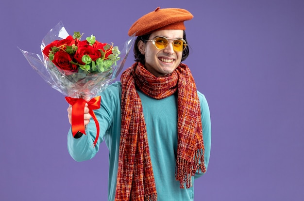 Glimlachende jonge kerel op valentijnsdag met hoed met sjaal en bril die boeket standhoudt op camera geïsoleerd op blauwe achtergrond