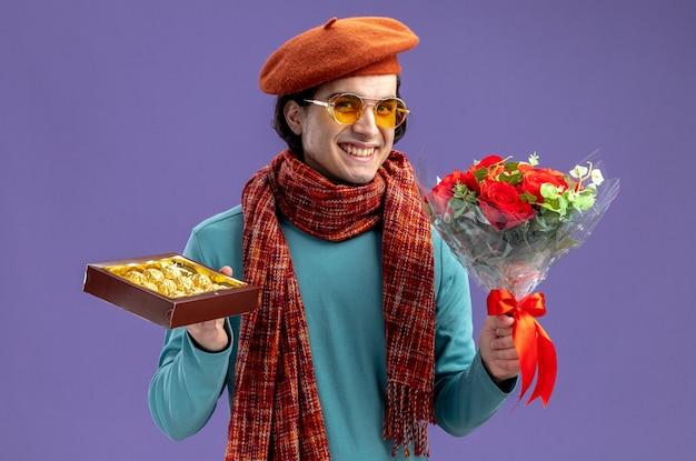 Glimlachende jonge kerel op valentijnsdag met hoed met sjaal en bril met boeket met doos snoep geïsoleerd op blauwe achtergrond