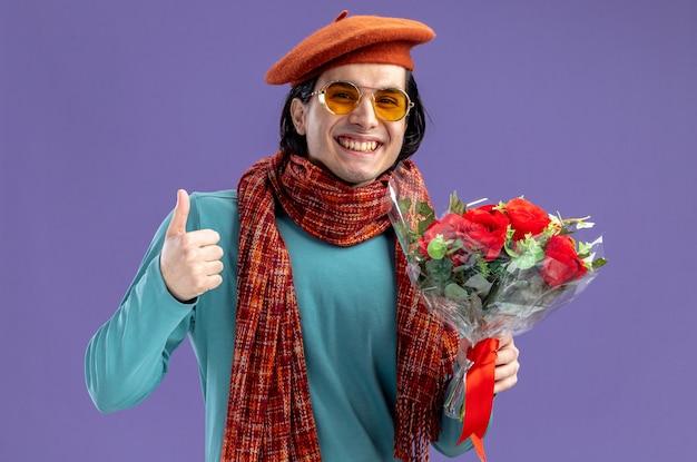 Glimlachende jonge kerel op valentijnsdag met hoed met sjaal en bril met boeket met duim omhoog geïsoleerd op blauwe achtergrond