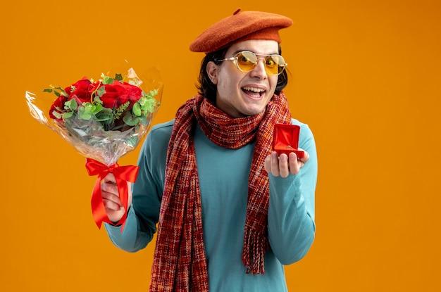 Glimlachende jonge kerel op valentijnsdag met hoed met sjaal en bril met boeket met trouwring geïsoleerd op oranje achtergrond