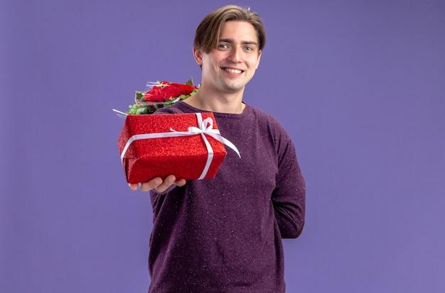 Glimlachende jonge kerel op valentijnsdag stak geschenkdoos op camera geïsoleerd op blauwe achtergrond