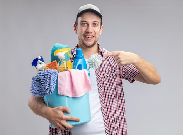Glimlachende jonge kerel schoner met dop en wijst naar emmer met schoonmaakgereedschap geïsoleerd op een witte achtergrond
