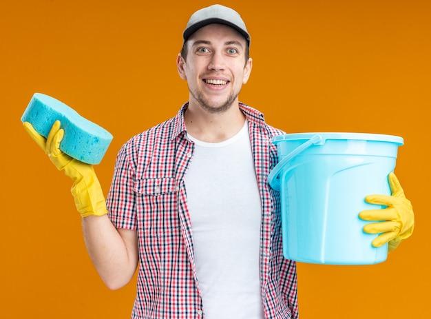 Glimlachende jonge kerel schoner met pet met handschoenen met spons met emmer geïsoleerd op oranje achtergrond