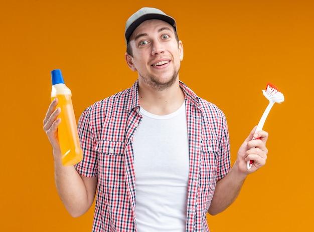 Glimlachende jonge kerel schoner met pet met reinigingsmiddel met borstel geïsoleerd op een oranje achtergrond