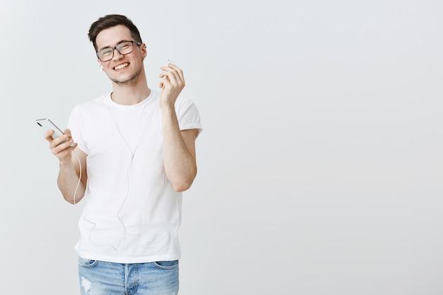 Glimlachende jonge kerelstart oortelefoon, die smartphone houdt