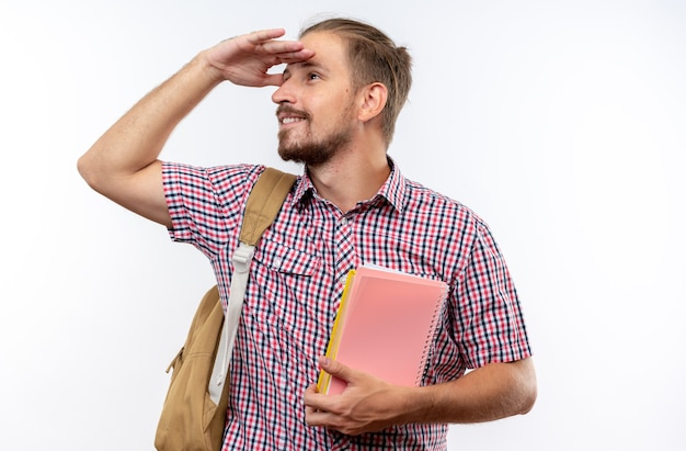 Glimlachende jonge kerelstudent die rugzak draagt die boeken houdt die afstand met hand bekijken die op witte muur wordt geïsoleerd
