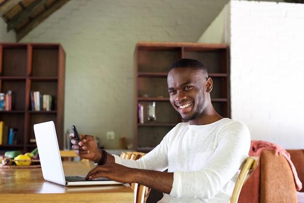 Glimlachende jonge kerelzitting bij lijst met celtelefoon en laptop
