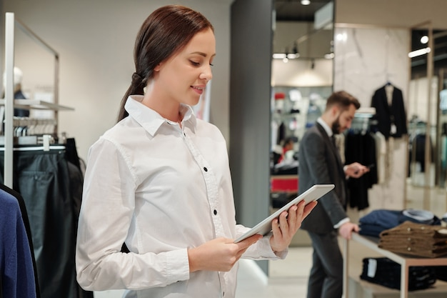 Glimlachende jonge kledingwinkelmedewerker die tablet gebruikt om naar leverancierscode te zoeken terwijl zakenman kleding kiest