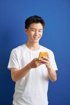 Glimlachende jonge knappe aziatische man die smartphone gebruikt om in contact te komen met familie en vrienden
