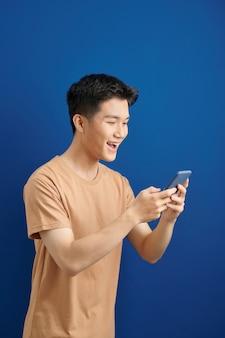 Glimlachende jonge knappe aziatische man die smartphone gebruikt om in contact te komen met familie
