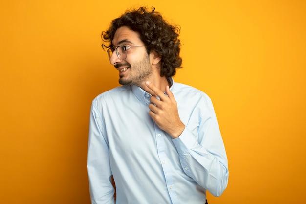Glimlachende jonge knappe blanke man met bril kijken en wijzend naar kant geïsoleerd op een oranje achtergrond met kopie ruimte