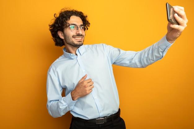 Glimlachende jonge knappe blanke man met bril nemen selfie geïsoleerd op een oranje achtergrond met kopie ruimte