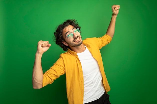 Glimlachende jonge knappe blanke man met bril vuisten omhoog geïsoleerd op groene muur met kopie ruimte