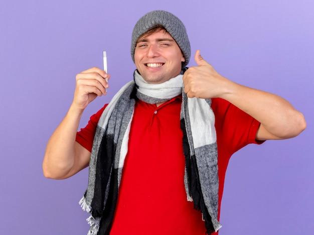Glimlachende jonge knappe blonde zieke man die de winterhoed en sjaal draagt die thermometer houdt die voorzijde toont die duim toont die omhoog op purpere muur wordt geïsoleerd