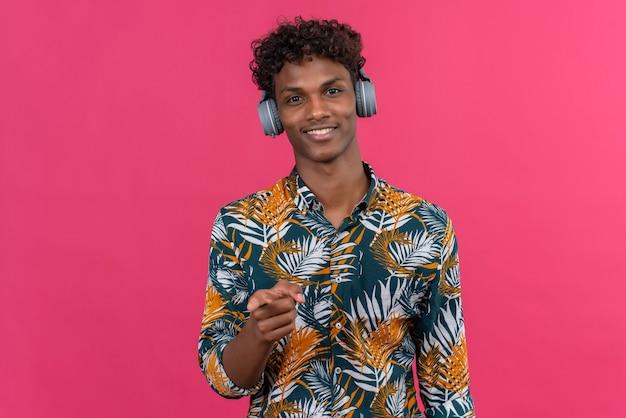 Glimlachende jonge knappe donkerhuidige man met krullend haar in bladeren bedrukt overhemd in koptelefoon wijzend met wijsvinger op camera op een roze achtergrond