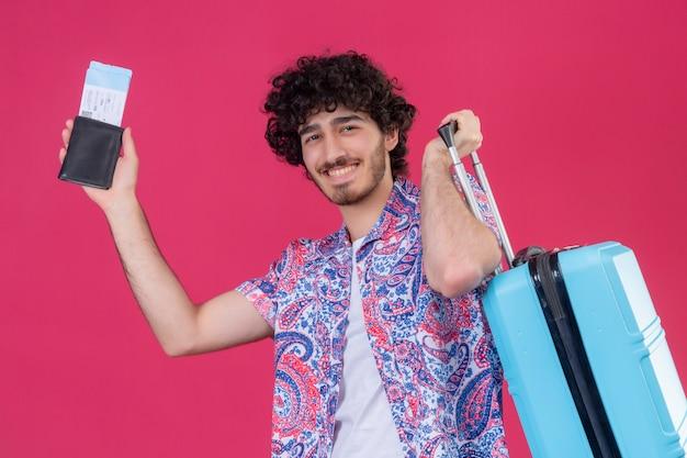 Glimlachende jonge knappe gekrulde reiziger man met portemonnee en vliegtuigtickets en koffer op geïsoleerde roze muur