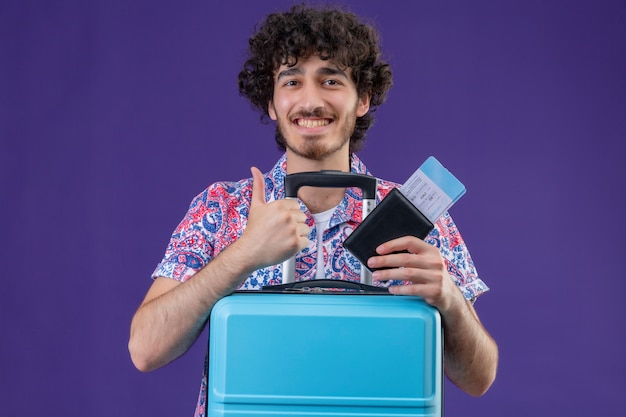 Glimlachende jonge knappe gekrulde reiziger man met vliegtuigtickets en portemonnee met koffer duim opdagen op geïsoleerde paarse muur