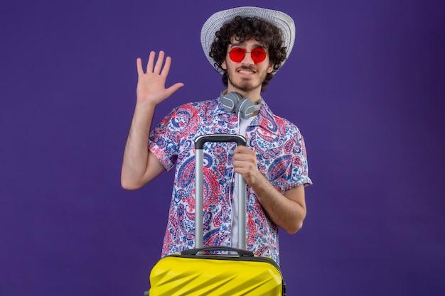 Glimlachende jonge knappe gekrulde reiziger man met zonnebril, koptelefoon op nek en hoed met koffer hallo gebaren op geïsoleerde paarse muur met kopie ruimte