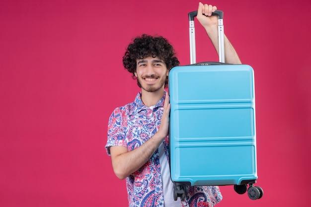 Glimlachende jonge knappe gekrulde reizigersmens die koffer opheft en hand erop op geïsoleerde roze muur met exemplaarruimte legt