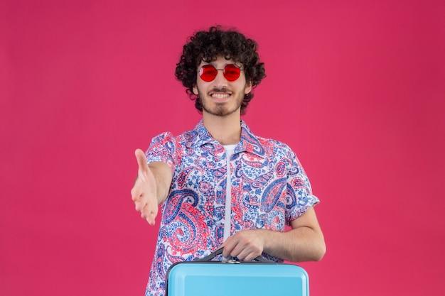 Glimlachende jonge knappe gekrulde reizigersmens die zonnebril draagt en hand uitstrekt hallo gebaren op geïsoleerde roze muur met exemplaarruimte