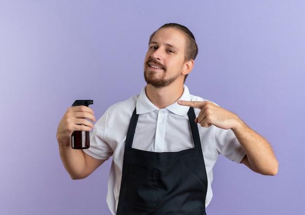 Glimlachende jonge knappe kapper die eenvormig bedrijf draagt en op sproeifles richt die op purpere muur wordt geïsoleerd
