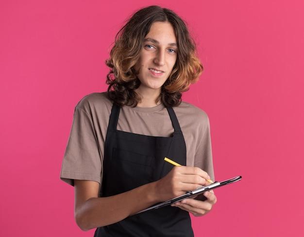 Glimlachende jonge knappe kapper die eenvormig schrijven met potlood op klembord draagt