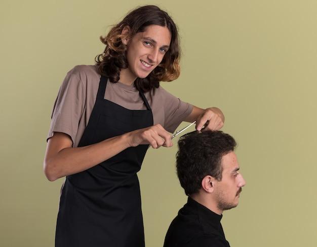 Glimlachende jonge knappe kapper die uniform draagt en kapsel doet voor zijn jonge cliënt geïsoleerd op olijfgroene muur