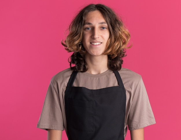Glimlachende jonge knappe kapper die uniform draagt