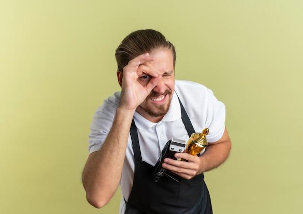 Glimlachende jonge knappe kapper met tondeuse en winnaar beker doen blik gebaar en knipogen geïsoleerd op olijfgroene muur