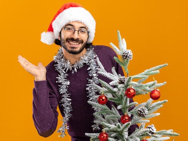 Glimlachende jonge knappe kerel die achter de kerstboom staat en een kerstmuts draagt met een slinger op de nek die de hand spreidt geïsoleerd op een oranje muur