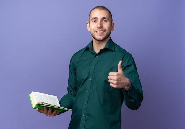 Glimlachende jonge knappe kerel die een groen overhemd draagt dat boek houdt dat duim toont